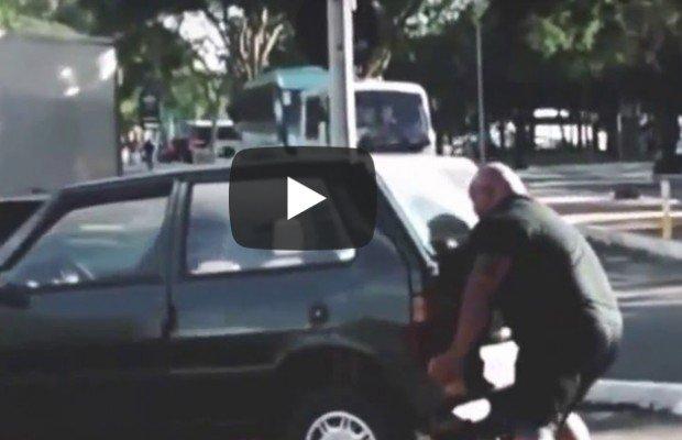 Un ciclista aparta con sus propias manos un coche aparcado sobre el carril bici