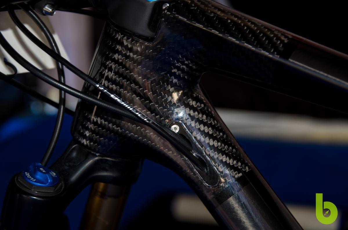 Es un secreto a voces que Mondraker, junto con su equipo profesional de mtb, está desarrollando una bici de doble suspensión para XC. Esta bici se encuentra a en la etapa final de desarrollo y, aunque aún puede sufrir algún cambio antes de salir al mercado, hemos tenido la suerte de fotografiar la Mondraker de Carlos Coloma de cerca y os traemos todos los detalles, componentes y peso.  El objetivo de Mondraker es conseguir una mountain bike con doble suspensión que pese menos de 9 kg y sea la referencia para el resto de fabricantes. Nosotros subimos a la báscula la bici de Carlos Coloma y aún le queda un poco para bajar de 9 kg, pero como decímos, no es la versión definitiva.   Mondraker XC doble suspensión Carlos Coloma  La Mondraker XC con doble suspensión de Carlos Coloma  Esta Mondraker de estética robusta pero de construcción ligera mantiene la estética de la marca con su potencia integrada y la continuidad en línea de su tubo superior hasta la rueda trasera. Podemos decir que el triangulo delantero es casi idéntido al del la actual Podium, pero es el sistema de suspensión trasera donde reside el potencial de esta mountain bike.  Mondraker XC doble suspensión Carlos Coloma  Durante la Copa del Mundo de Nove Mesto ya pudimos ver algunas imágenes de esta bici, pero ha sido durante el Campeonato de España cuando nos hemos acercado a verla en detalle y sin las decoración de camuflaje. Al no tener pegatinas ni pintura se puede apreciar mejor la disposición de la fibra de carbono a lo largo de todo el cuadro.  Mondraker XC doble suspensión Carlos Coloma  El amortiguador queda totalemente protegido por una coraza de carbono, la bieleta superior también es de carbono mientras que la inferior es de las pocas partes que está fabricada en aluminio. Con este sistema de Pivote virtual la bici responde con rigidez ante el pedaleo en subida y se vuelve ágil en zonas técnicas o de bajada.  Mondraker XC doble suspensión Carlos Coloma  El triangulo trasero se ha reforzado, en la